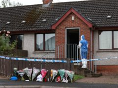 Forensics officers at the scene in Dungannon (PA)