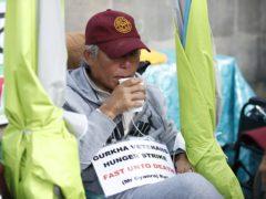 A Gurkha veteran drinks water during a hunger strike opposite Downing Street (Hollie Adams/PA)