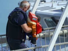 A young child is carried ashore as a group of people thought to be migrants are brought in to Dover, Kent, by Border Force officers, following a small boat incident in the Channel (Steve Parsons/PA)