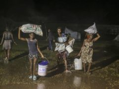 People affected by Saturday's earthquake walk under the rain of Tropical Depression Grace at a refugee camp in Les Cayes, Haiti (Joseph Odelyn/AP)