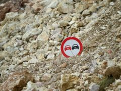 A traffic sign pokes out from the debris of a landslide triggered by Saturday's 7.2 magnitude earthquake, alongside a road in Rampe, Haiti (Matias Delacroix/AP)