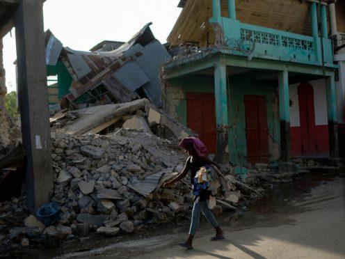 A woman walks past a collapsed building in Jeremie, Haiti (Matias Delacroix/PA)