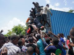 Residents overtake a truck loaded with relief supplies in Vye Terre, Haiti, on Friday (Fernando Llano/AP)