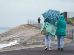 People hold umbrellas as they make their way along the sea front near Southsea beach in Hampshire (Andrew Matthews/PA)