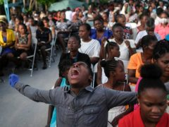 A parishioner shouts during a mass on the grounds next to an earthquake-damaged church in Les Cayes, Haiti (Matias Delacroix/AP)