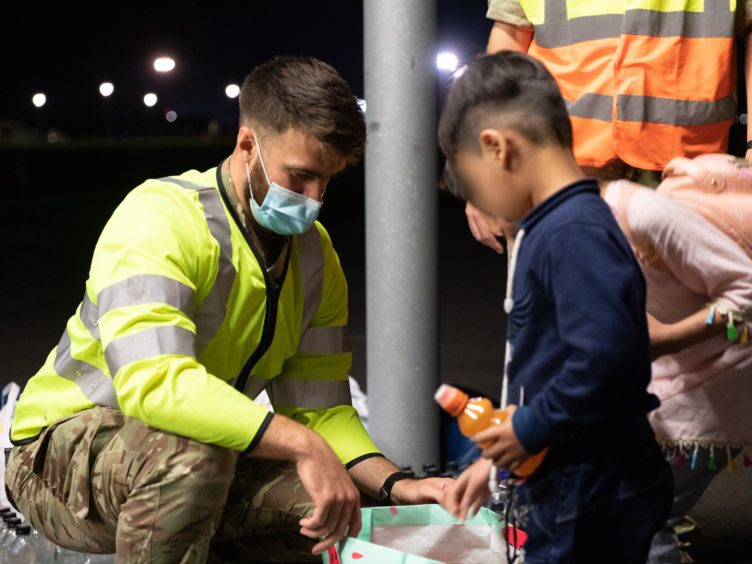Military personnel handing out food, drink, toys, and blankets during Operation Pitting at RAF Brize Norton to arrivals who have been evacuated from Afghanistan. (Cpl Will Drummee RAF/MOD/Crown copyright)