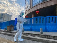 A worker in protective overalls outside the Wuhan Central Hospital (Ng Han Guan/AP)
