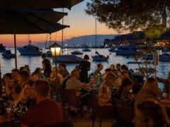 Holidaymakers sit in a seafront restaurant, in the Adriatic town of Rovinj, Croatia (Darko Bandic/AP)
