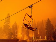 The Caldor Fire burns as a chairlift sits motionless at the Sierra-at-Tahoe ski resort (AP)