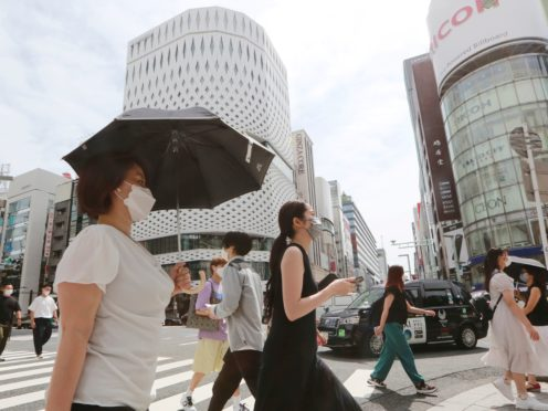 People wearing face masks walk along a street in Tokyo (Koji Sasahara/AP)