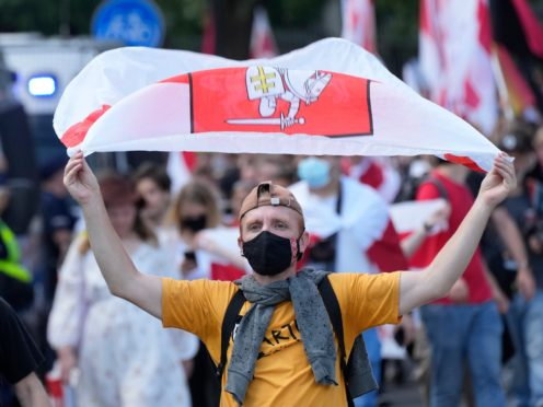 People carry banners of protest as they gather to denounce the regime of Belarusian President Alexander Lukashenko in Warsaw, Poland (Czarek Sokolowski/AP)