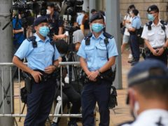 Police officers stand guard outside a court in Hong Kong (AP)