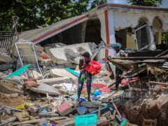 The death toll from the magnitude 7.2 earthquake that battered Haiti has risen to at least 1,297 as rescuers race to find survivors amid the rubble ahead of a potential deluge from an approaching storm (Joseph Odelyn/AP)