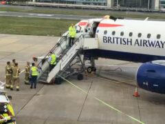 Paralympian James Brown lying top of a British Airways plane at City Airport, London (Extinction Rebellion/PA)