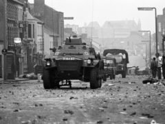 Armoured cars rumble over the rubble past overturned cars and a wrecked motor cycle at dawn in Belfast's Protestant Shankill Road, after a night of violence in which three people died.