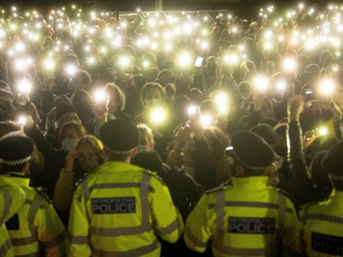 People in the crowd turn on their phone torches as they gather in Clapham Common for a vigil for Sarah Everard (PA)