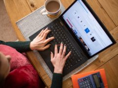 A woman using a laptop on a dining room table set up as a remote office (PA)