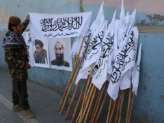 A Taliban fighter looks at Taliban flags in Kabul, Afghanistan (AP)