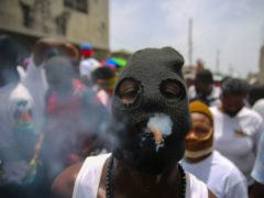 A member of the gang led by Jimmy Cherizier, alias Barbecue, a former police officer who heads a gang coalition known as G9 Family And Allies, joins a march to demand justice for murdered Haitian President Jovenel Moise (Joseph Odelyn/AP)