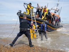 Immigration Enforcement officers and members of the RNLI assist a group of people thought to be migrants from an RNLI lifeboat after they were brought into Dungeness, Kent (Gareth Fuller/PA)