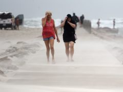 People in Texas shield their faces from wind and sand ahead of Hurricane Nicholas (Annie Rice/Corpus Christi Caller-Times via AP)