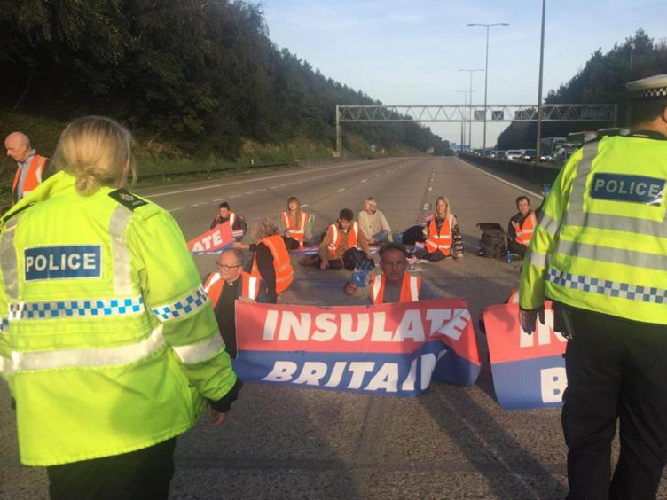Handout photo issued by Insulate Britain of protesters occupying the clockwise and anti-clockwise lanes on the M25 in Surrey on Tuesday (Insulate Britain/PA)