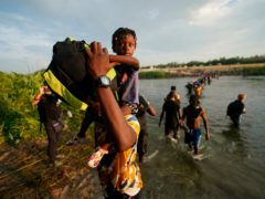 Migrants, many from Haiti, cross the Rio Grande from Del Rio, Texas, to return to Ciudad Acuna, Mexico, Tuesday, Sept. 21, 2021, to avoid deportation from the U.S. The U.S. is flying Haitians camped in a Texas border town back to their homeland and blocking others from crossing the border from Mexico. (AP Photo/Fernando Llano)