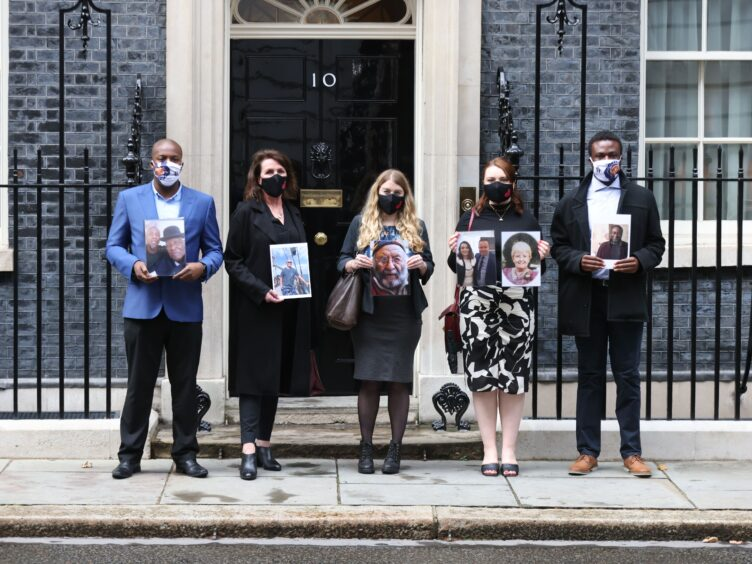 Members of the Covid-19 Bereaved Families for Justice group holding photos of loved ones outside 10 Downing Street, London, after their private meeting with Boris Johnson (James Manning/PA)