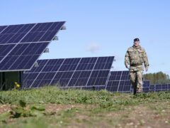 Sergeant Major Jimmy Girvan walks through a field of solar panels at the opening of the British Army's first ever solar farm (Danny Lawson/PA)