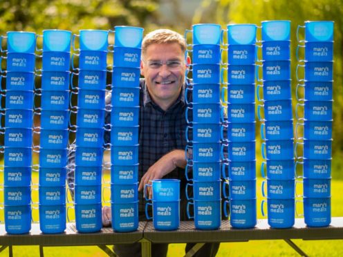 Magnus MacFarlane-Barrow founder and CEO of Marys Meals pictured next to mugs similar to those used by children receiving Marys Meals (Chris Watt/PA)