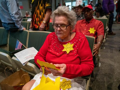 Christine Hill cuts out yellow Stars of David before an Anchorage Assembly meeting(Loren Holmes/Anchorage Daily News via AP)