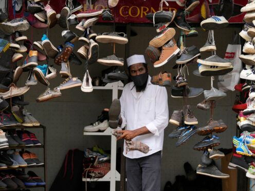 A man om Colombo displays used shoes for sale at his shop after easing of coronavirus restrictions in Colombo, Sri Lanka (Eranga Jayawardena/AP )