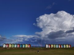 A rainbow appears behind the Blyth beach huts in Northumberland (PA)