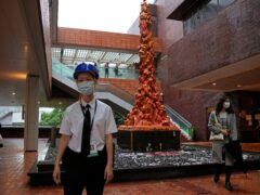 A security guard stands in front of the Pillar Of Shame statue (Kin Cheung/AP