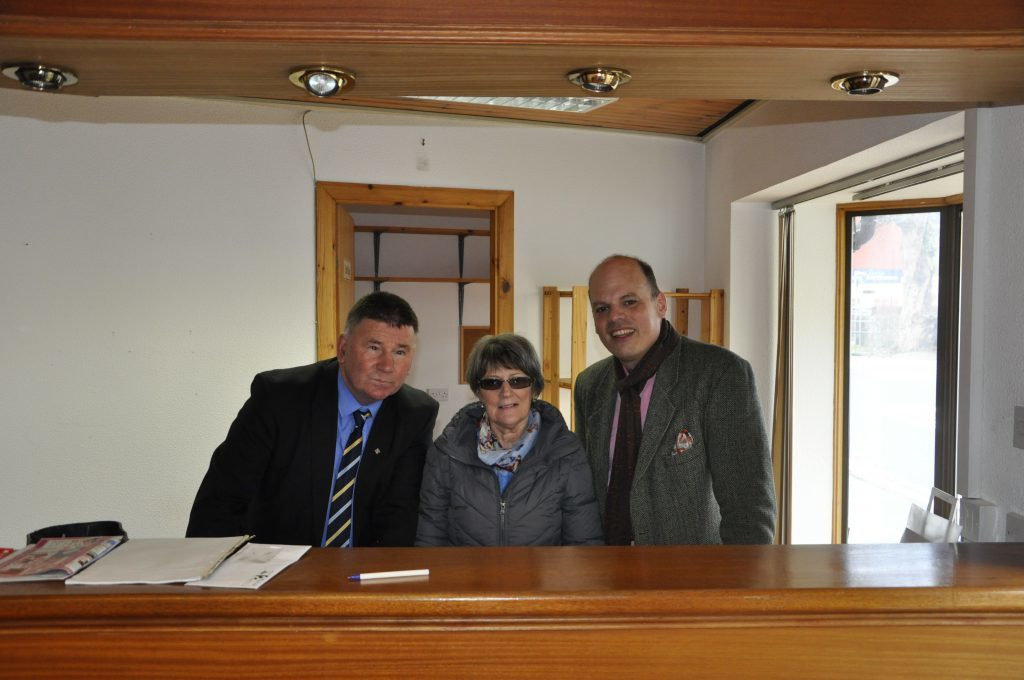 The three board members stand in front of the reception desk.