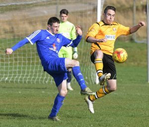 Fort's Alasdair Stark sweeps the ball away from his team's goalmouth, with Lossimeouth's Ross Archibald in pursuit. PICTURE IAIN FERGUSON, THE WRITE IMAGE. F15footy2noIF