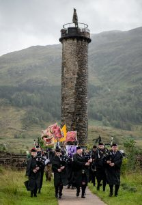 Lochaber Pipe Band opening the 2017 Glenfinnan Gathering with the 1745 monument in the background. Photograph: Abrightside Photography. F33 Glenfinnan Games 07JP.