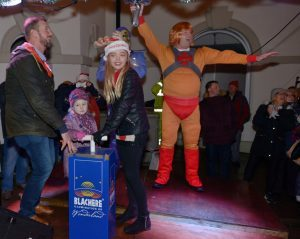 Raymond Harvey supervises as Poppie Lawson and Jenna Robertson push the plunger to light-up Campbeltown's streets watched by He-man.