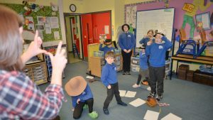 NTS trainer, Beth Morton, demonstrates how to given the illusion of using a camera to Emily at Gigha primary