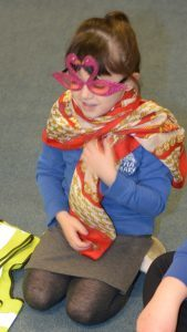 Laila experiments with a scarf and flamingo glasses.