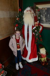 Ava, 7, with a model of Santa Claus.