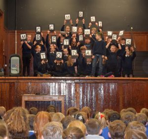 Pupils hold up letters spelling: 'MRS MCCORMICK RETIRES TODAY'. 50_c52mrsmccormick01