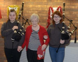 PSYV pipers Annabelle Allison and Mary Thomson accept a gift of chocolates from resident Sarah Elliot.