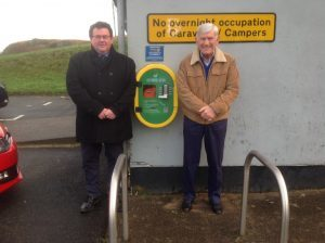 Oban Rotary Club president Tommy McQuade beside senior vice president Iain MacIntyre, and the newly installed defibrillator at Ganavan Sands.