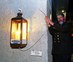 Matthew Ramsay lights the candle at the vigil held on the quay, Tarbert. Photo: Kevin Mcglynn