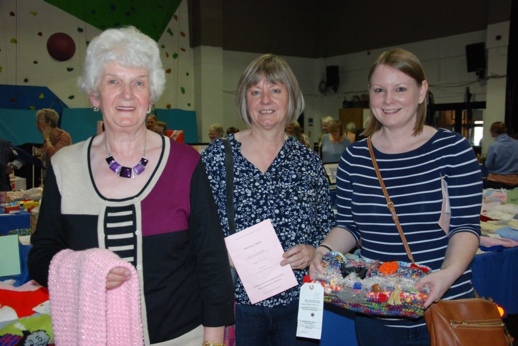 Oban SWI members (from left) Dinease Crowe, Lesley Crawford and Fiona MacPhee with some of their hand-crafted knitwear. 06_a17SWI_Argyll16