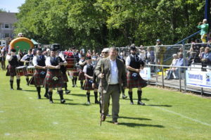 Chieftain David 'Jocky' Martin and committee member Linda Robb lead Mull and Iona Pipe Band onto the field.