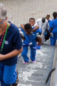 The first patient of the field service is carried up the gangway. Photo: Mercy Ships