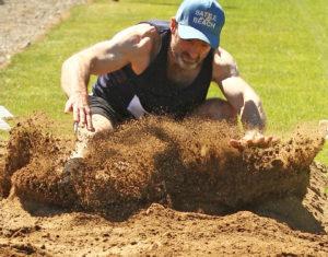 Oban High School PE teacher David McLaughlin hits the sand in the long jump competition. Photo Kevin McGlynn