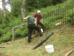 Michael MacNally and Ian Blythe work on replacing the fencing with metal railings.